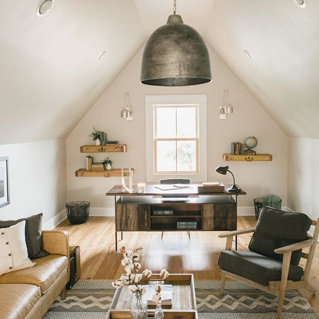 Attic Home Office Space With A Large Tin Pendant Lighting Fixture Hanging Above The Desk