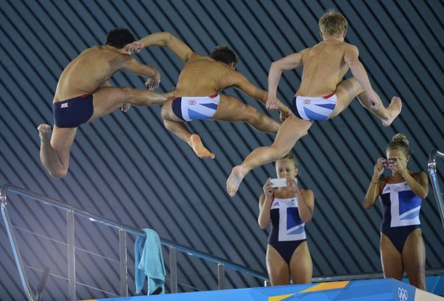 British divers Tonia Couch (R) and Sarah Barrow take photographs of Tom Daley (2nd L) and diving teammates from the 10 metre board at the Aquatics Centre in the Olympic Park in Stratford in east London July 26, 2012.