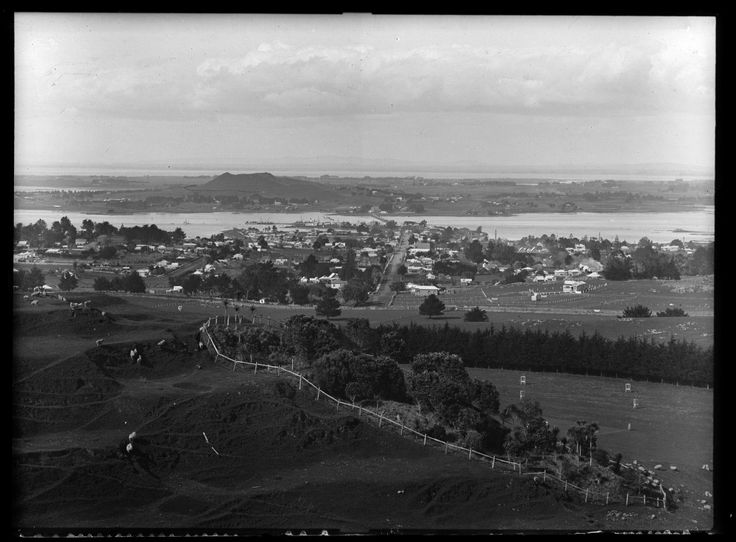 1906. Looking south east from One Tree Hill towards Mangere Mountain, showing Mangere Bridge, Onehunga Wharf and Onehunga township, Queen Street (centre), Selwyn Street (right), Mount Smart Road (left to right across centre). Sir George Grey Special Collections, Auckland Libraries, 1-W41.