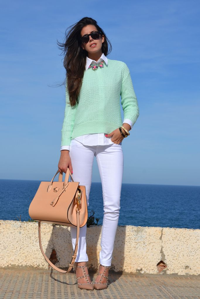 Mint sweater over a white collared shirt with white pants and nude pumps and bag