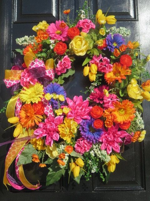 This handmade spring summer wreath certainly turned out very bright for the coming spring and summer seasons. The base is an 18 grapevine wreath to which I have added silk florals including hot pink geraniums and their foliage, orange, yellow and purple Gerber daisies, hot pink dahlias, orange ranunculus, white lilacs, and yellow mini tulips. Many florals in many colors that would be a welcoming focal point on your front door. The bow is comprised of three 1.5 wired ribbons; a pink and…