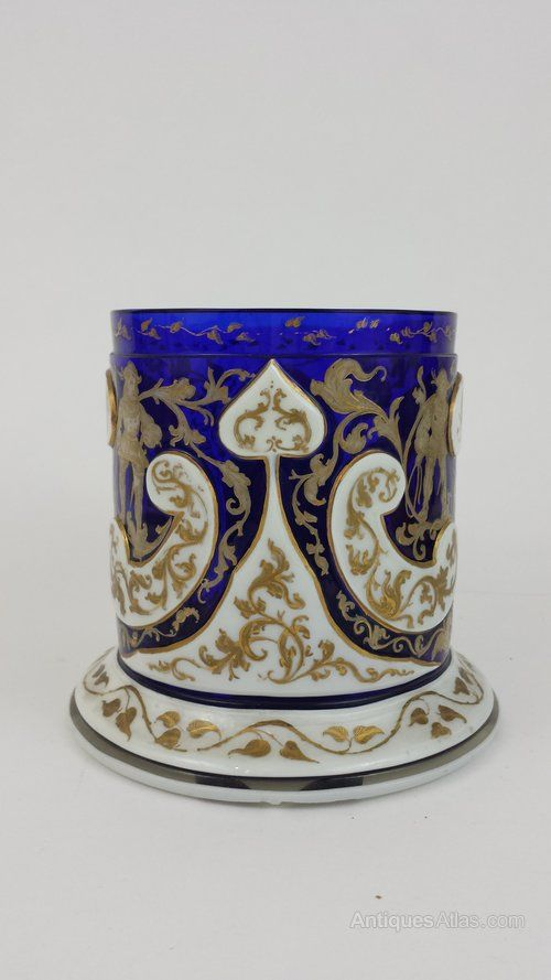 19th Century Bohemian glass mug overlaid with white and embust gold, the main body has drawing of men dressed in the traditional clothing and there are patterns leafs and branches on white, there is a small piece from base of the handle missing, otherwise in good condition.