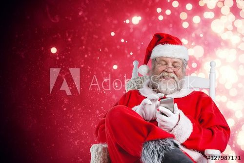 Composite image of happy santa claus messaging with mobile phone
