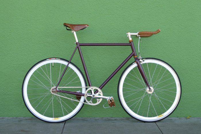 """Bicicleta fixie púrpura oscuro y terminaciones doradas. Disponible también como bicicleta híbrida en 6 velocidades. Manubrio de cuernos para una posición más deportiva. Puedes elegir el sillín de cuero Brooks o el café normal y agregar las punteras Plemons para mayor control. Piñón """"Flip-Flop"""" (fijo-libre) a partir de $199.900. Visita armatubici.cl !"""