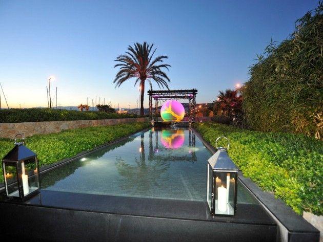Piscine extérieure en couloir de nage. Revêtement : CRYSTALROC HPM GRIS FONCE. Décoration en bout de piscine avec cette grande boule polyester. Crédit : Diffazur.