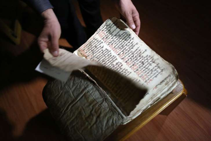 Raad Abdul-Ahed: In this Thursday, April 2, 2015 photo, Raad Abdul-Ahed, 45, who was displaced from his home by the advance of Islamic State militants, shows a centuries-old handwritten biblical manuscript in the old Syriac language in a small apartment room in the Kurdish city of Dahuk, northern Iraq. As Islamic State group militants advanced toward the monastery in northern Iraq last year, the monks were determined to protect a fragile, vital piece of their heritage: They sent their…