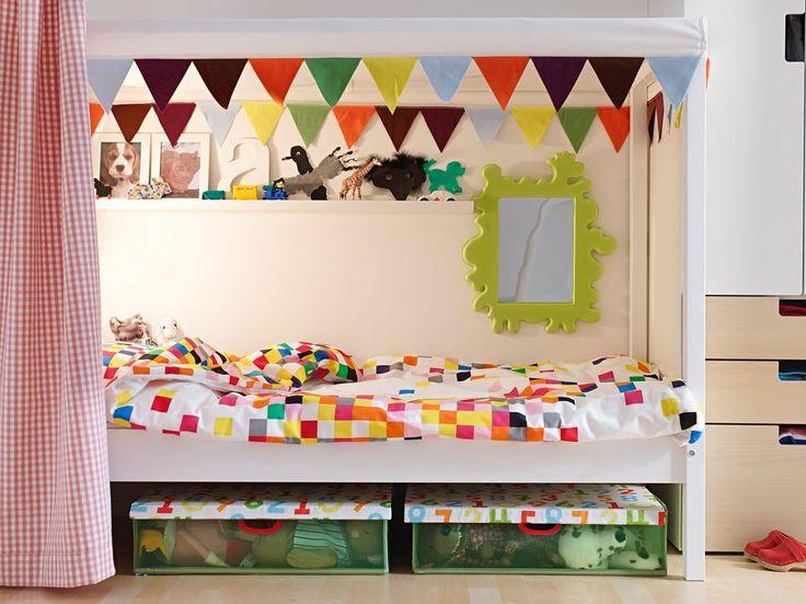 Idées déco chambre enfant : lit et ciel de lit övre fanions, rideau Vichy rouge, miroir vert, caisse de rangement en plastique sous le lit - Ikea