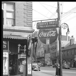 Curry's Drug Store, 167 West Short (corner of Upper); ext store front & nearby buildings;  L.H. Lewis & Co. Real Estate (150 West Short); Central Barber Shop (154 West Short); Milner Hotel (114-118 West Short); Rich-Lee Beauty School (124 West Short); Office Equipment Co. (128 West Short); American Dry Cleaners (130 West Short); Modern Beauty Shop (134 West Short); Curry Jas H Restaurant (140 West Short) - Kentucky Digital Library