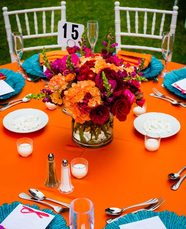 Bright orange and turquoise tropical destination wedding table setting.