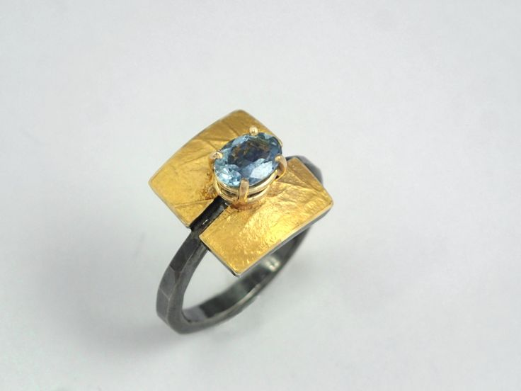 Precious gold and silver ring with an aquamarine stone rough surface and…