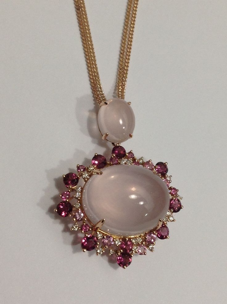 The stunning matching pendant to the ring; a cabochon cut rose quartz surrounded by dazzling white diamonds and pink tourmalines set in rose gold.