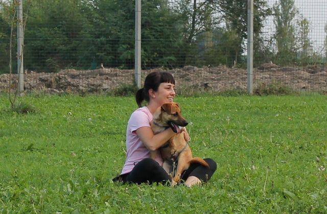 Serena, educatrice in formazione, tiene il cucciolo dal rifugio che fa il corso. / Serena, an apprentice dog trainer, hugs a little pup from the shelter who's also taking the class.