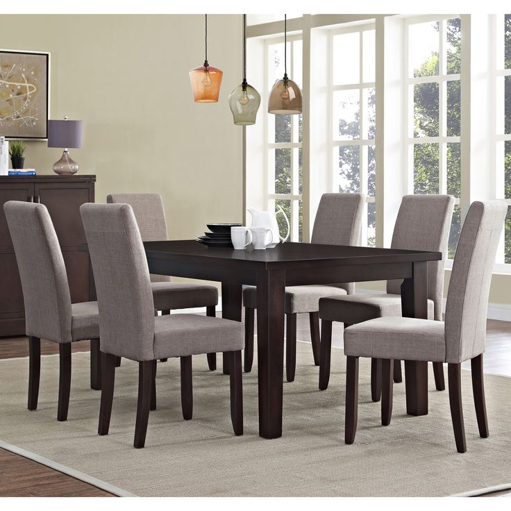 Dine in sophisticated style with this 7-piece Wydenhall Normandy Dining Set. Six chairs fit comfortably around the java finished table. The chairs are available in a variety of upholstery colors and materials.