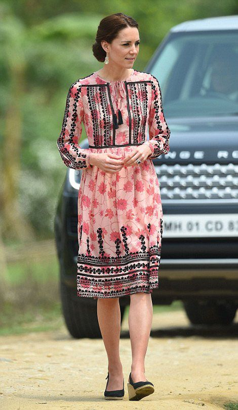 Catherine, Duchess of Cambridge in a pink Topshop dress with a tassel neck tie, floral print and Indian-inspired embroidery.She paired the frock with black wedge espadrilles and swept-back hair to meet Indian villagers.