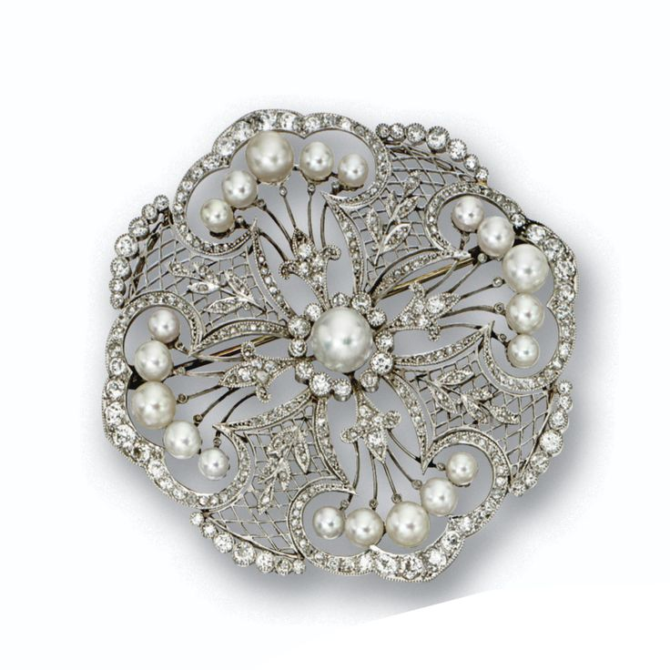 DIAMOND AND CULTURED PEARL BROOCH, CIRCA 1915. The modified circular plaque of lace design accented with foliate sprigs against latticework grounds, set with numerous small old-mine and rose-cut diamonds and with 21 cultured pearls measuring approximately 7.5 to 4.0 mm., mounted in platinum.