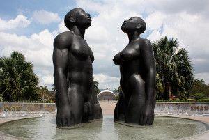 """Canção da Redenção, Jamaica. O monumento da artista Laura Facey, mostra um casal negro nu, em bronze, 3 m de altura, olhando para o alto representando sua ascensão triunfal aos horrores da escravidão. A base da escultura é uma fonte, a água brota do centro e cai sobre a superfície curva. A artista inspirou-se nas palavras do herói nacional Marcus Garvey – """"ninguém, somente nós mesmos podemos libertar nossas mentes"""" – presentes, também, na letra de Redemption Song, de Bob Marley."""