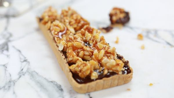 Recipe with video instructions: This peanut butter and chocolate tart is the perfect dessert to impress!  Ingredients: Pastry:, 200g plain flour, 100g butter, 50g (1) egg, pinch salt, Filling:, Peanut butter, 250g dark chocolate, 250ml double cream, Topping:, 250g caster sugar, Peanuts