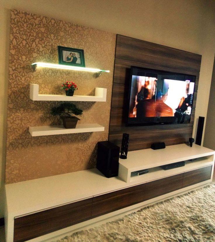 Sala pequena decorada com painel de tv, rack, prateleiras  tapete.