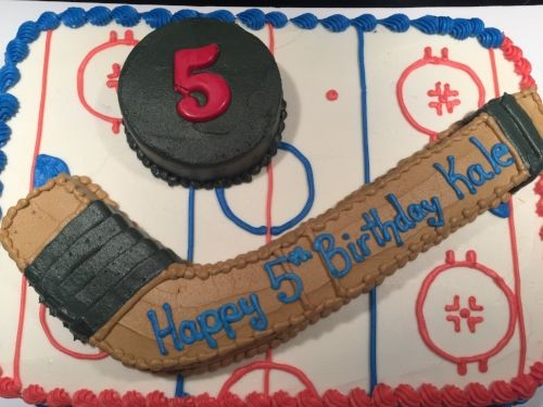 Hockey themed cake equipped with stick and puck!