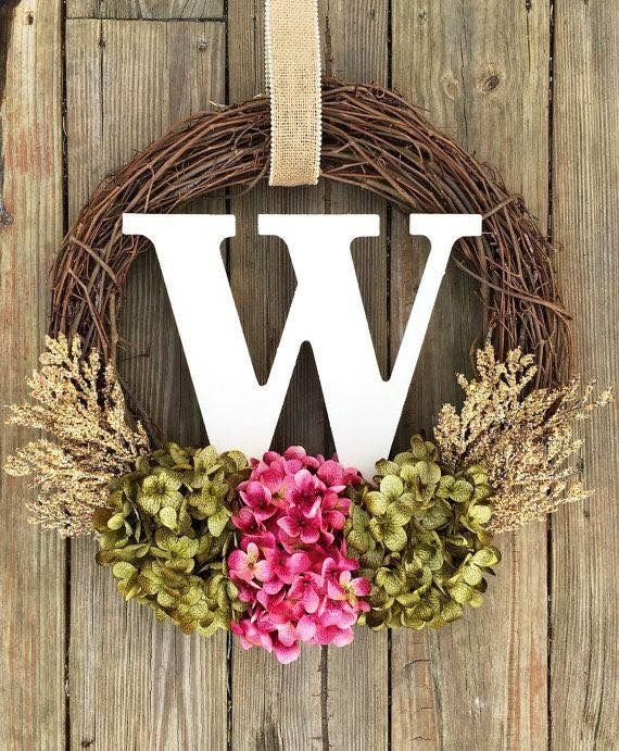 Front door family initial wreath made from grape vine wreath, wooden letter, dried flowers.