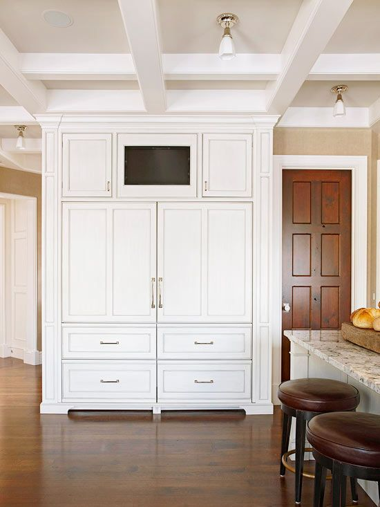 Bulky, unsightly appliances are a thing of the past. This large refrigerator -- covered with white cabinet panels that match the rest of the kitchen -- conceals the fridge and freezer drawers' identity while maintaining a seamless look in the kitchen. The handles of the refrigerator and freezer drawers also match the rest of the kitchen's hardware, which adds to the seamless style.