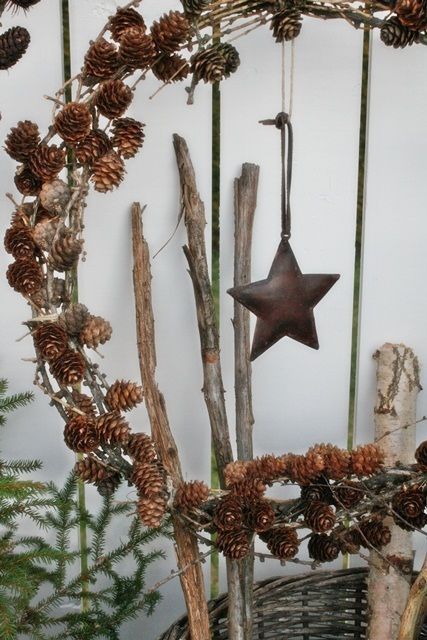Pine cone wreath. Love the thin single wire frame with small scale pine cones and a large diameter. I prefer the simplicity of no ornaments.