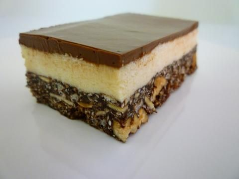 Not Your Average Nanaimo Bar. Why? From the top down: single origin Ecuadorian chocolate ganache, real butter and tahitian vanilla cream - light as a feather, and the base filled with pecans, almonds, and coconut. (Riso - gluten free options.)