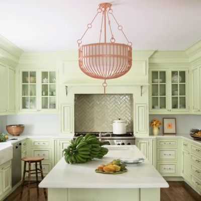 A bright kitchen with light green cabinets, white countertops, a herringbone tile backsplash, and a pink light fixture