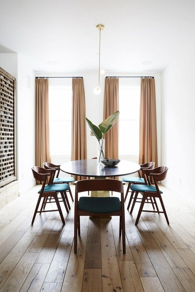 Dining room with light wood floors, floor to ceiling curtains, and a midcentury modern table