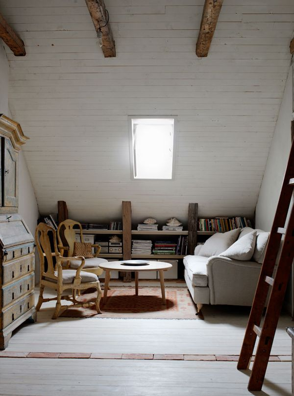 attic room, beams, nice architecture, deep sofa, traditional designs (chair), table, low bookshelves, one slanted window,
