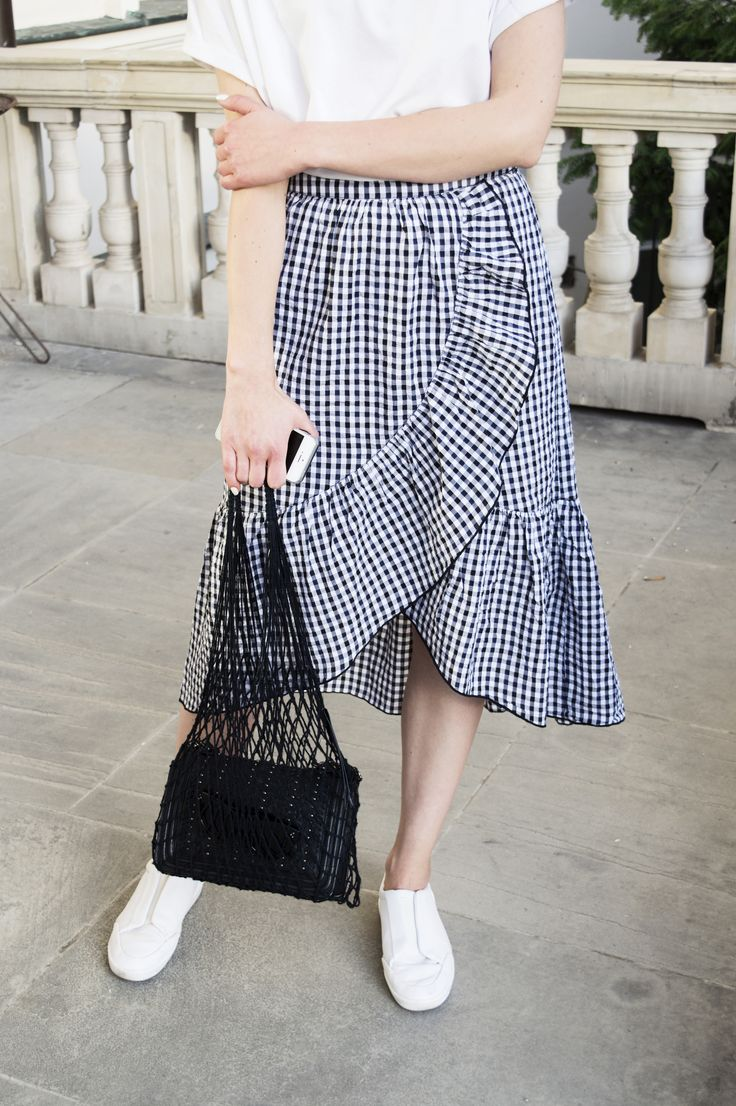 Mango black&white flouncy skirt, minimal jewelry, white T-shirt and black Ania Kuczynska net bag. More on afnewsletter.com