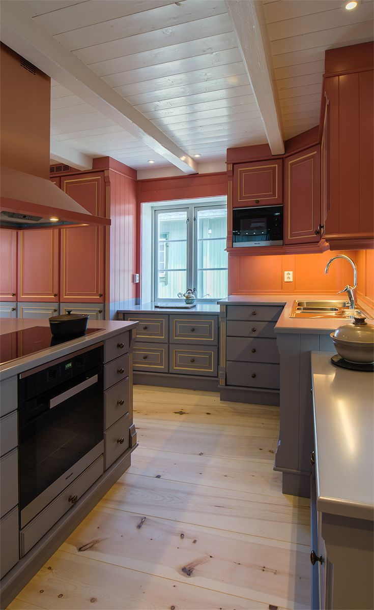 The owners of this house wanted the kitchen to match the colors on the wall. Handpainted in red/pink og grey/blue, with decorpaintings in gold.