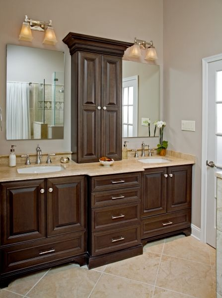 The vanity area provides a warm, rich feel with its dark cherry cabinetry, and it contrasts with the light and airy feeling of the rest of the space. The crown molding adds drama to the space. Roman T