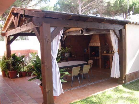 Ref.8301 Alquiler de chalet independiente en la urbanización Las Mogarizas, La Barrosa, Chiclana de la Frontera, Cádiz. En el exterior de la finca, la cual está ajardinada y arbolada, hay un porche delantero amueblado y cerrado con clistaleras, zona de piscina cercada (con piscina de 8 x 4 m., cuarto de baño y tumbonas), duchas, solarium y una magnifica barbacoa comedor toda techada con pérgola de madera.