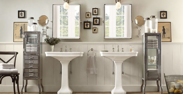 Pedestal sinks, wainscoting and chair w/ bath cabinet.