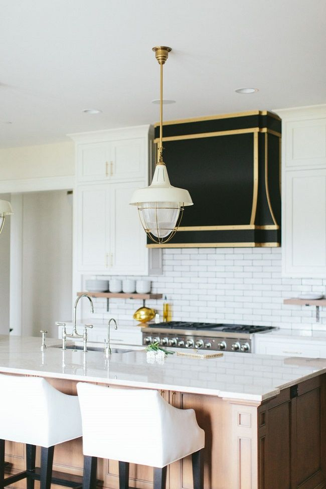 black range hood with brass piping and mixed metal accents in the kitchen love the