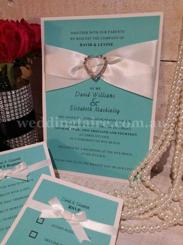 Nothing says love more than Tiffanys!  Here is a stunning A5 invitation embellished with a 33mm diamante heart buckle with two strands of satin ribbon, adorning a Tiffany's coloured card and all mounted on a 216gsm white card.  Accessorise with lolly buffet tags, place card, table numbers or personalised chocolate bars.
