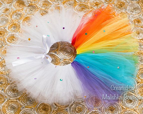 PLEASE NOTE THAT THIS LISTING IS FOR TUTU ONLY. THE ROMPER AND OTHER ACCESSORIES ARE NOT INCLUDED BUT ARE AVAILABLE FOR SALE IN MY SHOP. Such a unique and beautiful handmade tutu with bright attractive colors! This tutu is all white with a rainbow colored tail in the back that is longer. This tutu is very full and is finished off with colorful rhinestones all over. Ties in the front to make a pretty bow. Pair this with my beautiful Rainbow Romper, Headband and barefoot sandals Shown above…