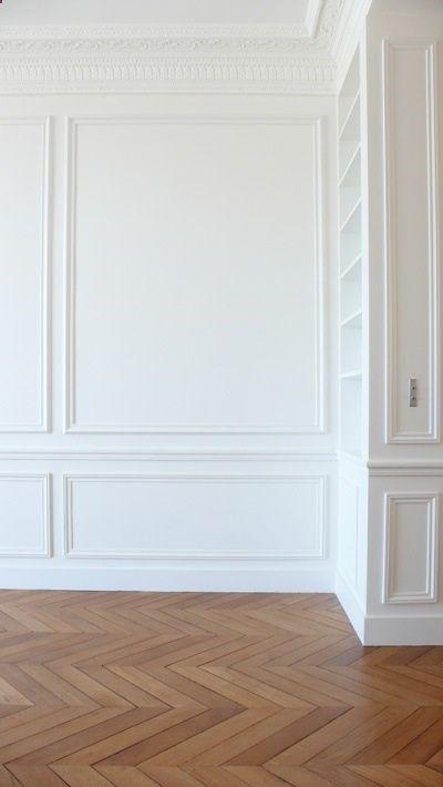 Classic white space with gorgeous mouldings & oak herringbone floors