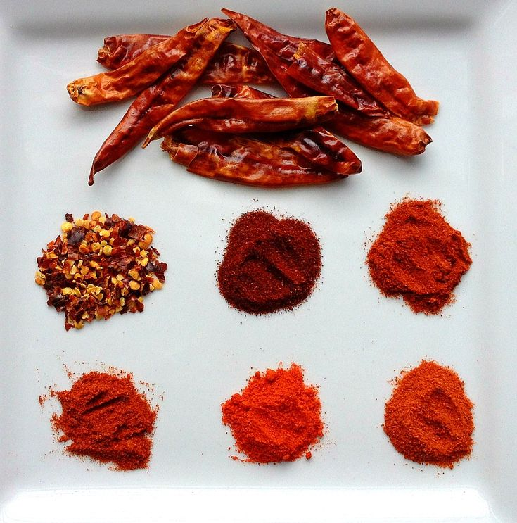 Different red chilli peppers, from the top, going left to right: whole dry red chillies, crushed red pepper, ancho chile powder, paprika, basic hot chilli powder, kashmiri red chilli powder, ground cayenne powder