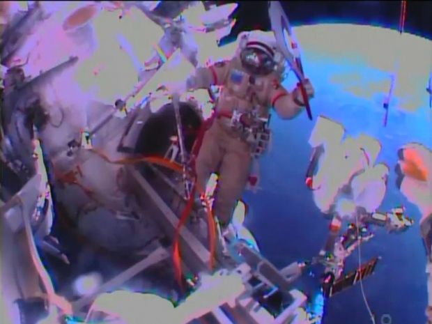 Russian astronaut Oleg Kotov holds an Olympic torch as he begins a spacewalk outside the International Space Station on Nov. 9, 2013. A pair...