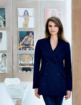Alessandra Rich in porter magazine, winter 2014, with framed photos from 1973's pirelli calendar on display in her dining room behind her