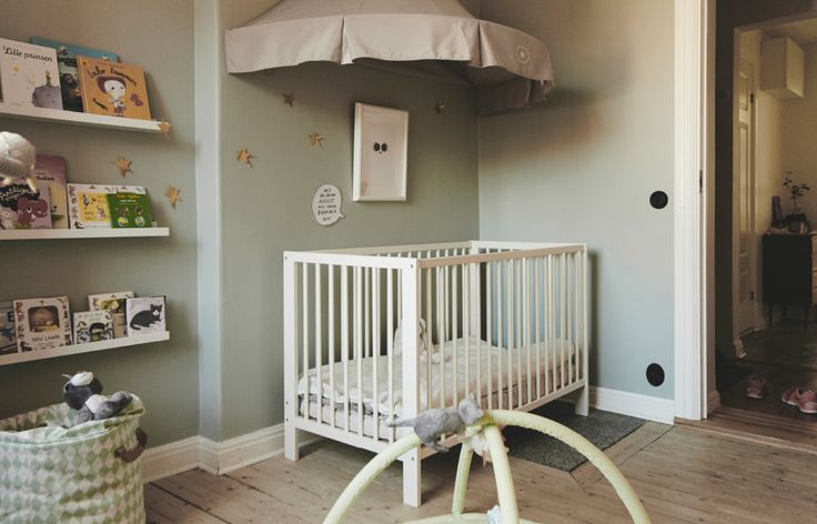 Make a nursery sleeping area with a cot that converts to a bed under a cosy grey canopy decorated with golden stars.