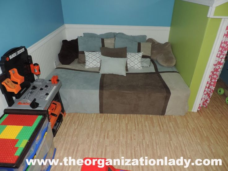 The spare bed was incorporated into the playroom design and the children of the house enjoy hiding under the pillows and using the bed as a trampoline! While the flooring may look like wood in the pictures it is actually wall to wall faux wood play mats, perfect for soft landings and easy on the eyes!!! The corner playhouse was constructed to help enclose the bed/trampoline and was a perfect fit for the play kitchen and houses larger items such as shopping carts and strollers when not in…