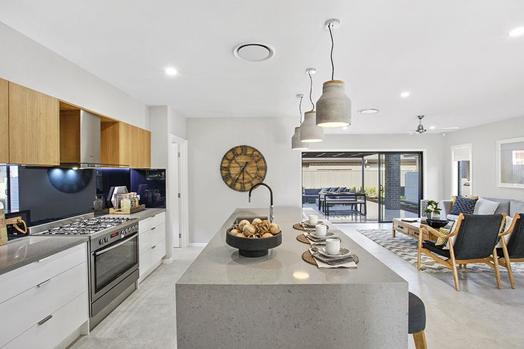 Kitchen. Waterfall edge stone benchtop. Glass splashback. Grey pendant lights. Timber cupboards. Laminex.