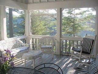 screened porch - notice board and batten detail above, solidity of posts, rails and balusters = enveloping comfort and generational continuity = deep seated feeling of continuance and tradition even if its brand new.