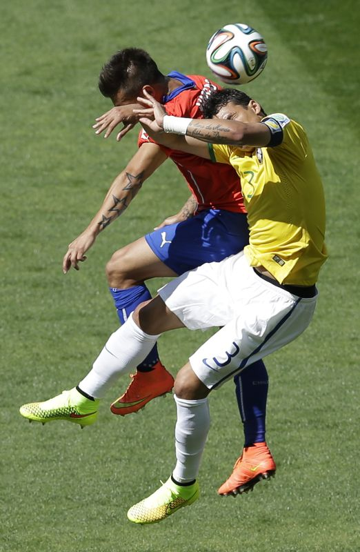 Chile's Eduardo Vargas, left, and Brazil's Thiago Silva go for a header during the World Cup round of 16 soccer match between Brazil and Chile at the Mineirao Stadium in Belo Horizonte, Brazil, Saturday, June 28, 2014. (AP Photo/Hassan Ammar)