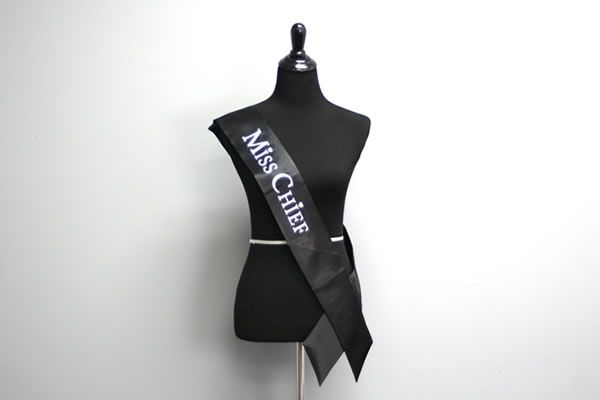 """Miss Chief - Sassy Pageant Sash Sash for a funny and sassy made-up beauty pageant Velcro closures Tailored at the shoulder for a custom-like fit Material: satin Colors: Black (white letters), Red (black letters), and White (black letters) Size: Standard Adult 4"""" x 70"""" (10 cm x 178 cm) View more Sassy Beauty Pageant Sashes Sale Price: $19.95"""