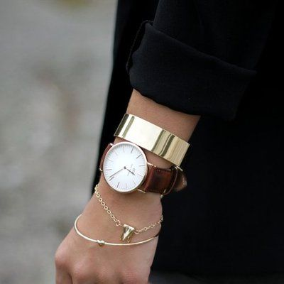 Gold bangles and a brown leather strap watch make a simple stacked look