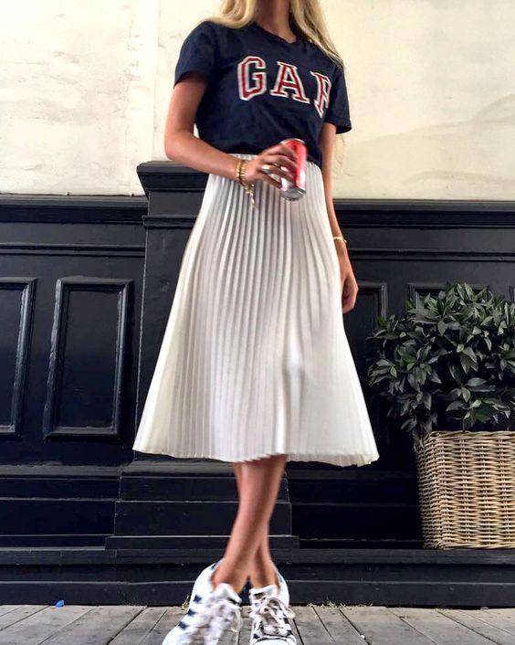 Qu'elle soit longue ou midi, cet été il n'y a qu'une seule façon de porter la jupe plissée. Et c'est avec des baskets. Si on désire marquer la taille, on p